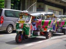 Tuk-tuk fährt auf Straße in Bangkok, Thailand mit einem Taxi Lizenzfreies Stockfoto