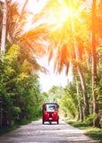 Tuk-tuk rojo debajo de las palmeras en la carretera nacional Foto de archivo