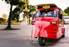 Tuk rosso luminoso Tuk in priorità alta con la statua Defocused di Buddha è fotografie stock libere da diritti