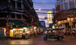 Tuk tuk和商店Yaowarat路的有它繁忙的交通的,氖S 免版税库存图片