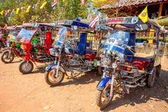 Tuk tuk在乌隆他尼省,泰国的寺庙之外停放了 免版税库存照片