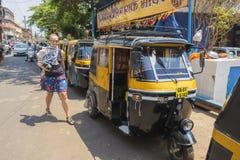 Tuk-tuk是一辆小黄色出租汽车在路和在城市  库存照片