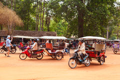Tuk-tuk in Angkor Wat, Cambodia. Angkor Wat, Cambodia - March 19, 2011 : Cambodian tuk-tuk drivers waiting for tourists for a ride across the temples of ancient Stock Photography