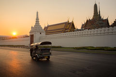 Tuk tuk. Tuk-Tuk drive on street and background of Wat Phra Kaew ( the Temple of the Emerald Buddha) in morning. Here is destinations of landmarks traveler stock images