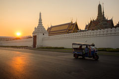 Tuk tuk. Tuk-Tuk drive on street and background of Wat Phra Kaew ( the Temple of the Emerald Buddha) in morning. Here is destinations of landmarks traveler stock photo