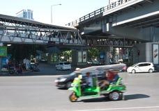 Tuk-tuk driving in business area of bangkok. Tuk-tuk with foreign passenger driving in business area of bangkok Stock Photo