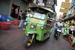 A Tuk-Tuk Taxi on a Chinatown Street in Bangkok. A three wheeled  tuk-tuk taxi drives along a road in Chinatown on March 2, 2012 in Bangkok, Thailand. There are Stock Photo