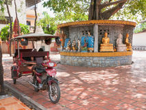 Tuk-tuk taxi at temple in Phnom Penh. Cambodian style tuk-tuk taxi parked in the shade under a tree at Wat Svay Dang Kum in central Phnom Penh Stock Image