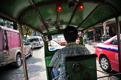 Tuk Tuk Taxi. View from the interior of a tuk tuk taxi as its driver naviages a busy city centre road on June 1, 2013 in Bangkok, Thailand. Tuk tuks are Stock Images