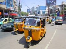 Tuk tuks and cars on city street Stock Photos
