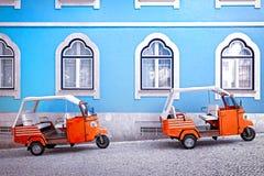 Tuk tuk voertuig voor de blauwe voorgevelbouw in Lissabon, Portugal stock foto