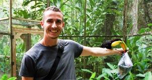 Tukanvogel auf Männer ` s Arm im Keilschwanzsittich-Gebirgsvogel-Park, Honduras lizenzfreie stockfotos