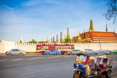 Tuktuk泰国在街道的出租汽车停车处有后面地面鲜绿色菩萨寺庙的(Wat phra kaew) 库存图片