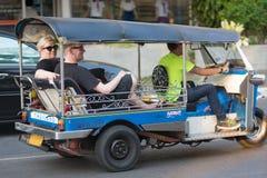 Tuktuk driver drives tourists, Bangkok Stock Image