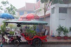 Tuktuk motocycle在雨季风期间在Kampot 免版税图库摄影