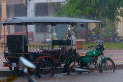 Tuktuk motocycle during rain monsoon in Kampot. Tuktuk during rain monsoon in Kampot Cambodia Stock Image