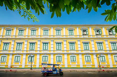 Tuktuk taxi in front of yellow building Stock Images