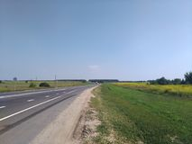 Summer russian fields, road, blue sky, green and yellow grass Royalty Free Stock Photography