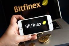 Tula, Russia - 28 agosto 2018: sulla pila di cryptocurrencies con il logo verde di scambio di Bitfinex nel fondo E fotografia stock libera da diritti