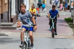 TULA, RUSSIA - JUNE 1, 2014: Teenagers riding bicycles on sidewalk in summer city at sunny day with selective focus. Main subject is watching in camera and stock photography