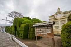 TULCAN, ECUADOR - JULI 3, 2016: sommige installatiesbeeldhouwwerken bij de ingang van de begraafplaats naast een houten teken met Stock Fotografie