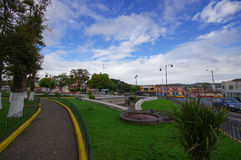 TULCAN, ECUADOR - JULY 3, 2016: some autos driving on the street next to an empty park on a cloudy day Royalty Free Stock Photography