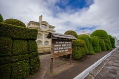TULCAN, ECUADOR - JULY 3, 2016: some vertical graves behing the topiary sculptures and a wood sign with a phrase on it.  Royalty Free Stock Photography