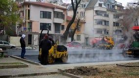 TULCEA, ΡΟΥΜΑΝΊΑ - 31 ΟΚΤΩΒΡΊΟΥ: Εργάτες οικοδομών που ισοπεδώνουν το φρέσκο πεζοδρόμιο ασφάλτου σε μια κατασκευή διαδρόμων ως τμ απόθεμα βίντεο