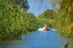 TULCEA, ROMÊNIA - EM SETEMBRO DE 2015: Os povos não identificados tomam a viagem do barco com uma guarda florestal local na reser fotos de stock
