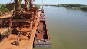 Industrial cargo port with operating cranes on the Danube river, aerial view stock footage