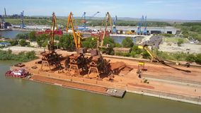 Industrial cargo port with operating cranes on the Danube river, aerial view stock video
