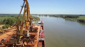 Industrial cargo port with operating cranes on the Danube river, aerial view stock video footage