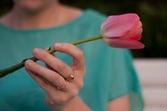 Tulipán rosado en la mano izquierda de la mujer Gir en el vestido verde l con joyería en los fingeres que sostienen una flor Imagen de archivo