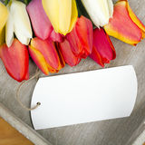 Tulip bouquet and blank card on wooden tray Stock Photo