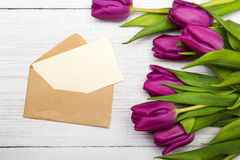 Tulip bouquet and envelope on white wooden background Royalty Free Stock Image