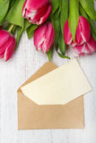 Tulip bouquet and envelope on white wooden background Royalty Free Stock Photos