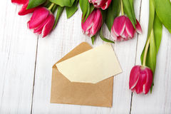 Tulip bouquet and envelope on white wooden background Royalty Free Stock Photography