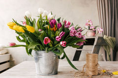Tulip bouquet. Floristry workplace background. Colorful flowers, tools set in white interior. Preparation for the creation of bunch. Florist, decorator, diy Royalty Free Stock Photo