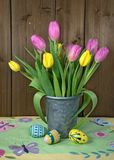Tulip bouquet in metal bucket. Pink and yellow tulip bouquet in gray metal pail with Easter eggs on spring tablecloth royalty free stock photo