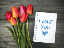 """Tulip bouquet and notepad with words """"I love you"""" Royalty Free Stock Photography"""