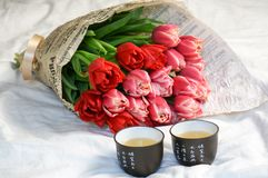 Tulip bouquet and tea cups on white sheets stock image