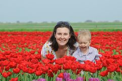 In Tulip Field. Mother with son in tulips field Stock Photo