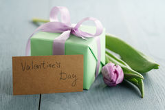 Tulip flower with green gift box and paper card on blue wood table for valentines day Stock Photography