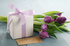 Tulip flower with white gift box and paper card on blue wood table for valentines day Royalty Free Stock Photo