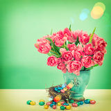 Tulip flowers and chocolate easter eggs. Vintage style toned pic Royalty Free Stock Photo