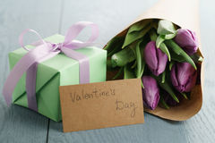 Tulip flowers with green gift box and paper card on blue wood table for valentines day Royalty Free Stock Photo