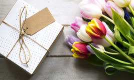 Tulip Flowers and Present with Design Space Empty Tag on Wooden royalty free stock photography
