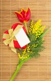 Tulip, mimosa, gift in heart form and card Stock Photography