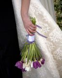 Tulip wedding bouquet. Close-up of bride's hand with wedding ring holding her purple and white tulip bouquet down at her side Stock Image