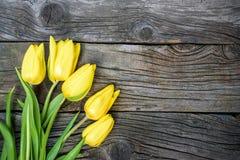A tulipa amarela fresca floresce com a toalha na tabela de madeira do vintage antigo Fotos de Stock